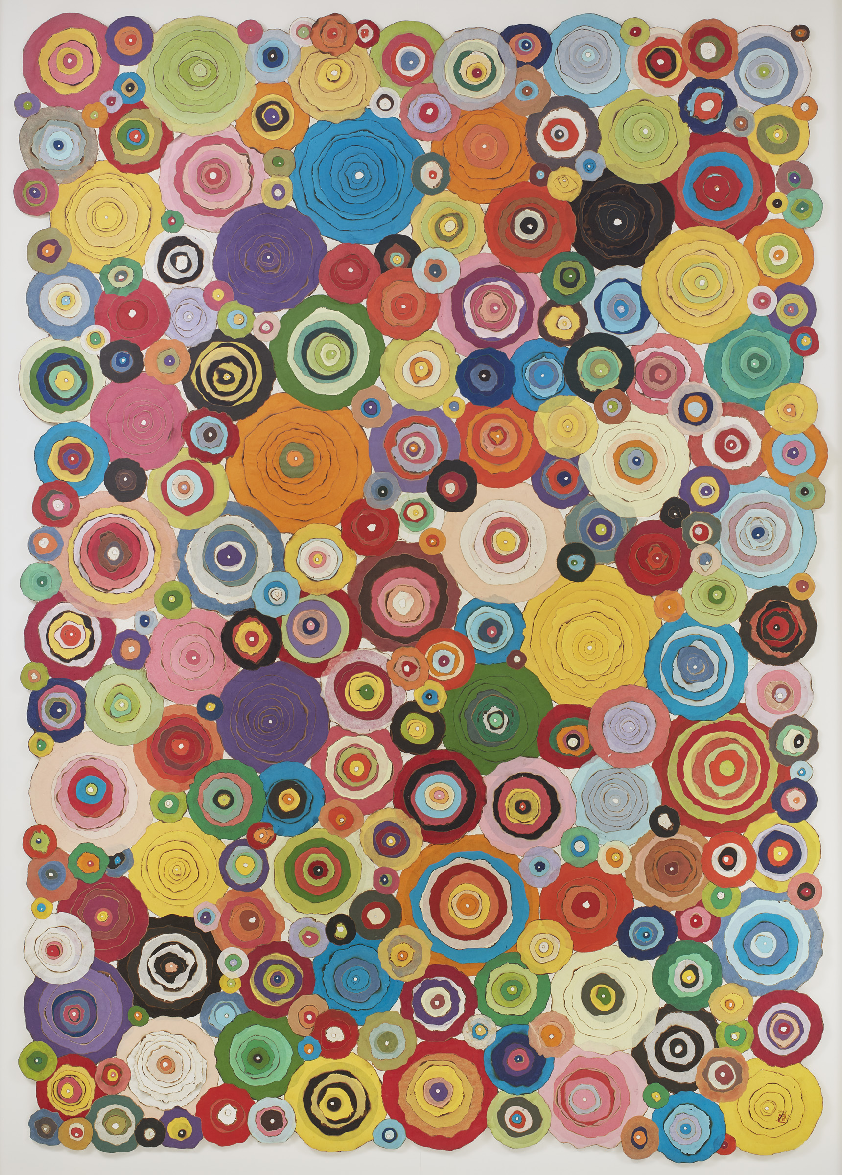 Numerous different colored circle shaped pieces of paper stacked to create a collage.